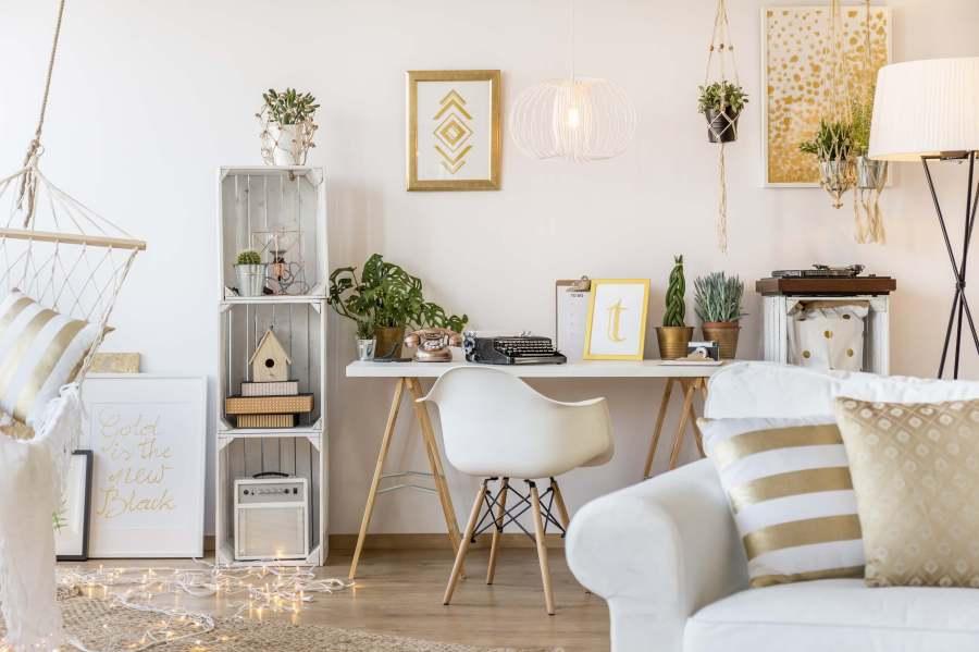 Bureau dans un salon au tons blancs et beige avec une touche de doré